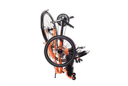 Side, right folded view of Catrike 5.5.9 recumbent trike in atomic orange for easy transport