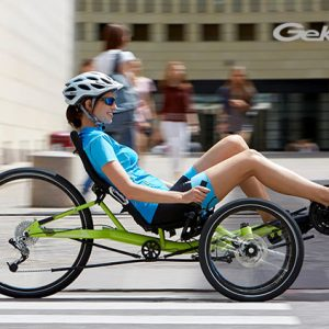 Smiling white woman side view on lime green recumbnet trike from HP Velotechnik